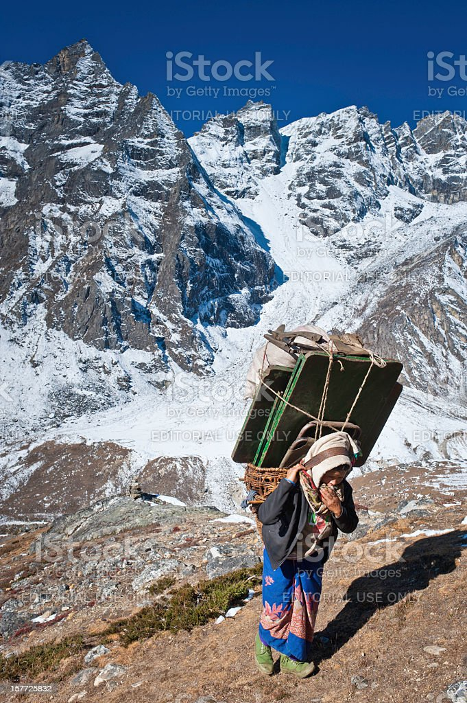 Female Sherpa porter carrying heavy load in mountains Himalayas Nepal royalty-free stock photo
