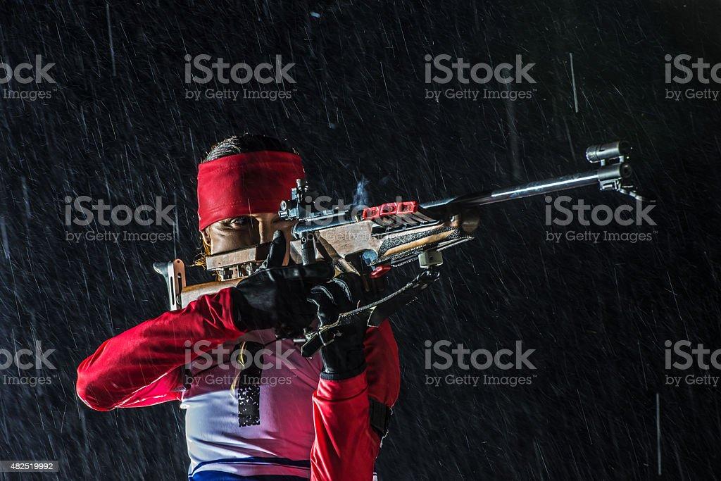 Female shooting at biathlon training at night stock photo