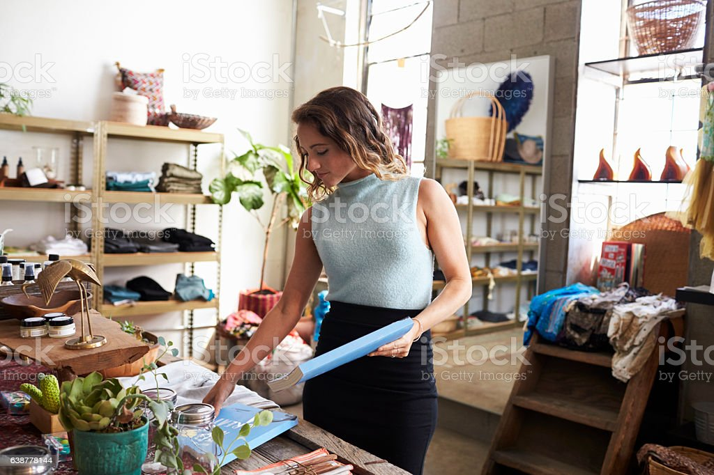 Female shop assistant arranging a clothes shop display stock photo