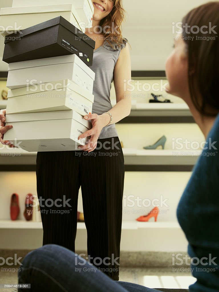 Female shop assistant bringing woman stack of shoe boxes, smiling royalty-free stock photo