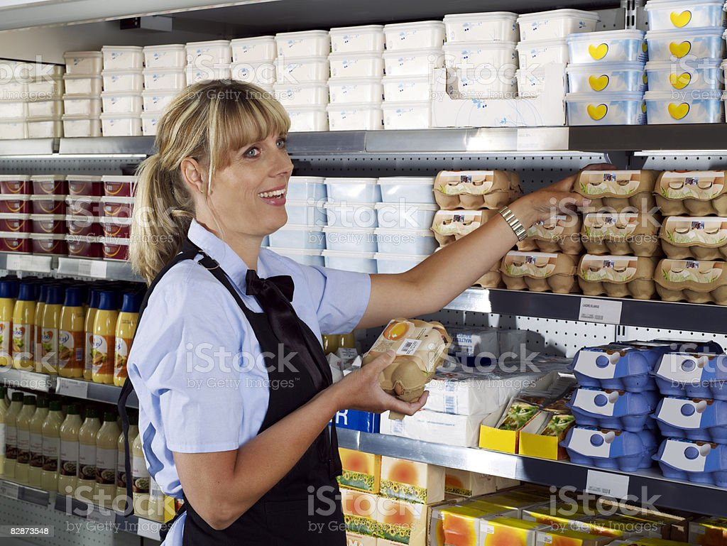 Female shop assistant putting eggs into display stock photo
