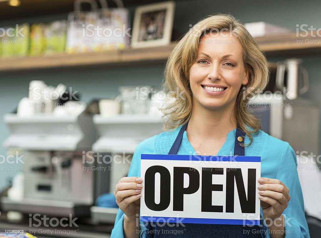 Female Shop Owner Holding an Open Signboard royalty-free stock photo