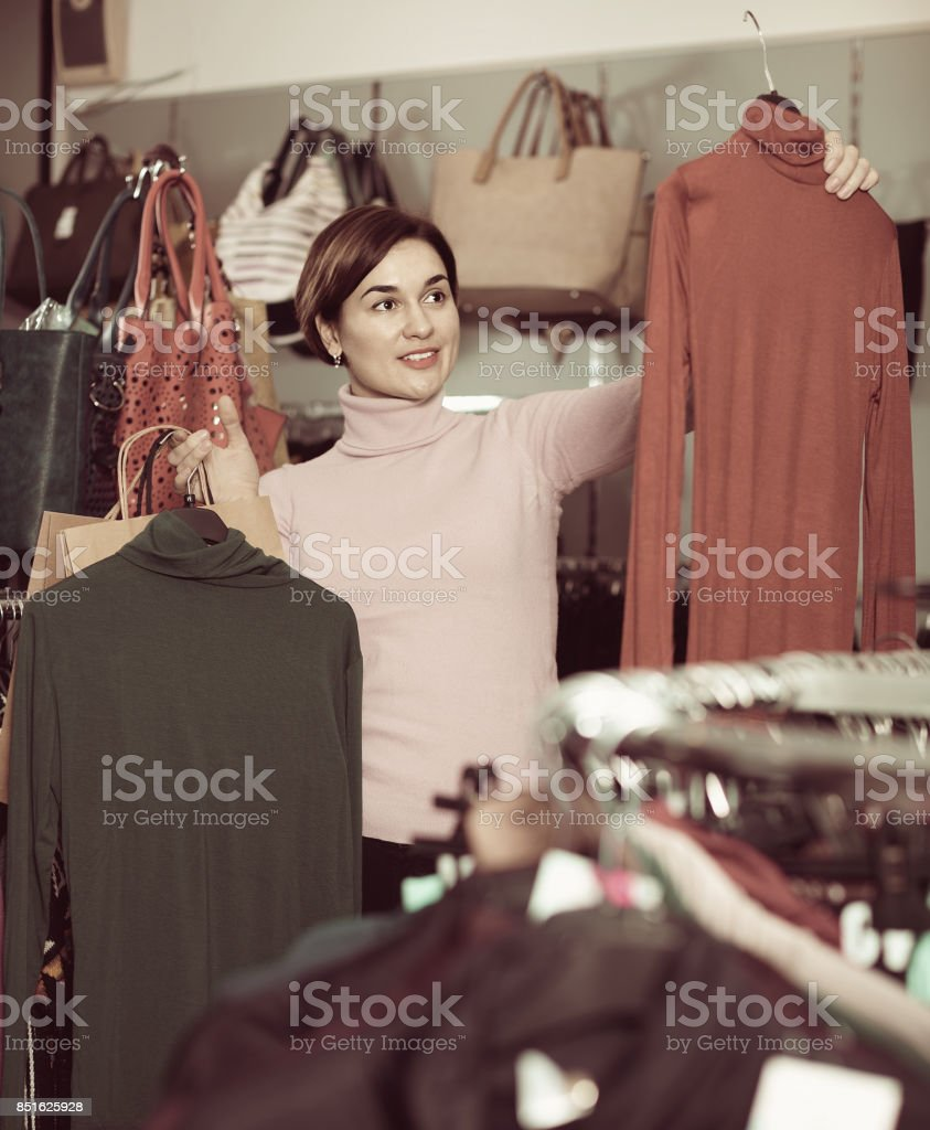 Female shopper examining turtleneck sweaters in women's cloths shop stock photo