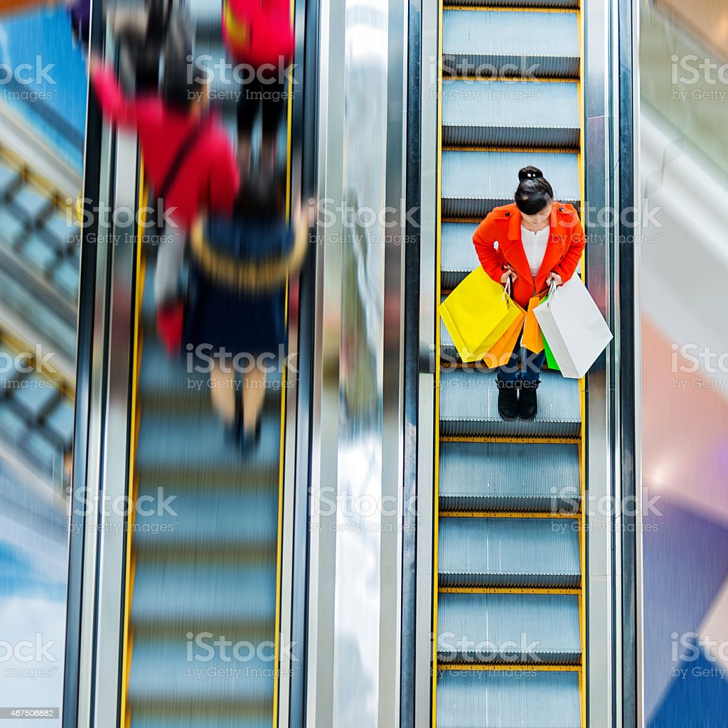 Female shopper standing on escalator with many shopping bags stock photo