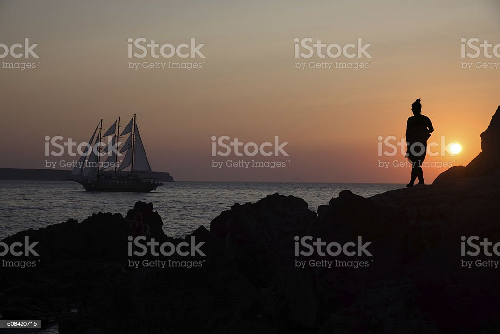 Female Silhouette and sailing boat at sunset in Santorini stock photo