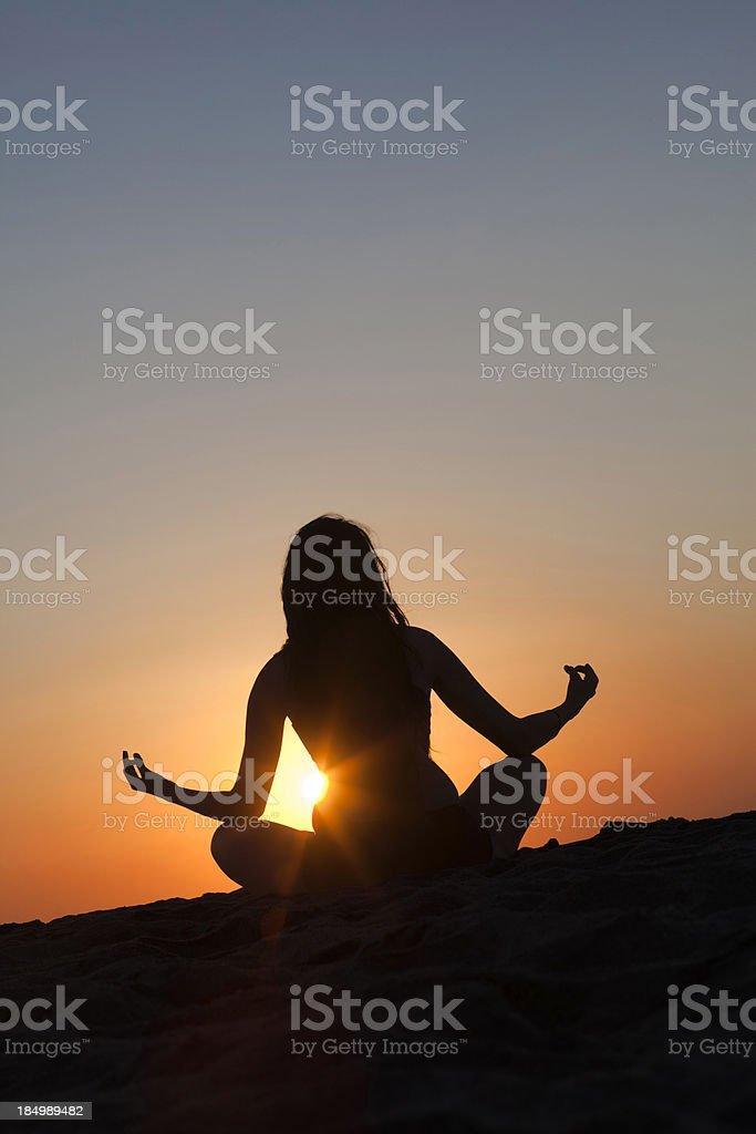 female silhouette doing yoga at sunrise royalty-free stock photo
