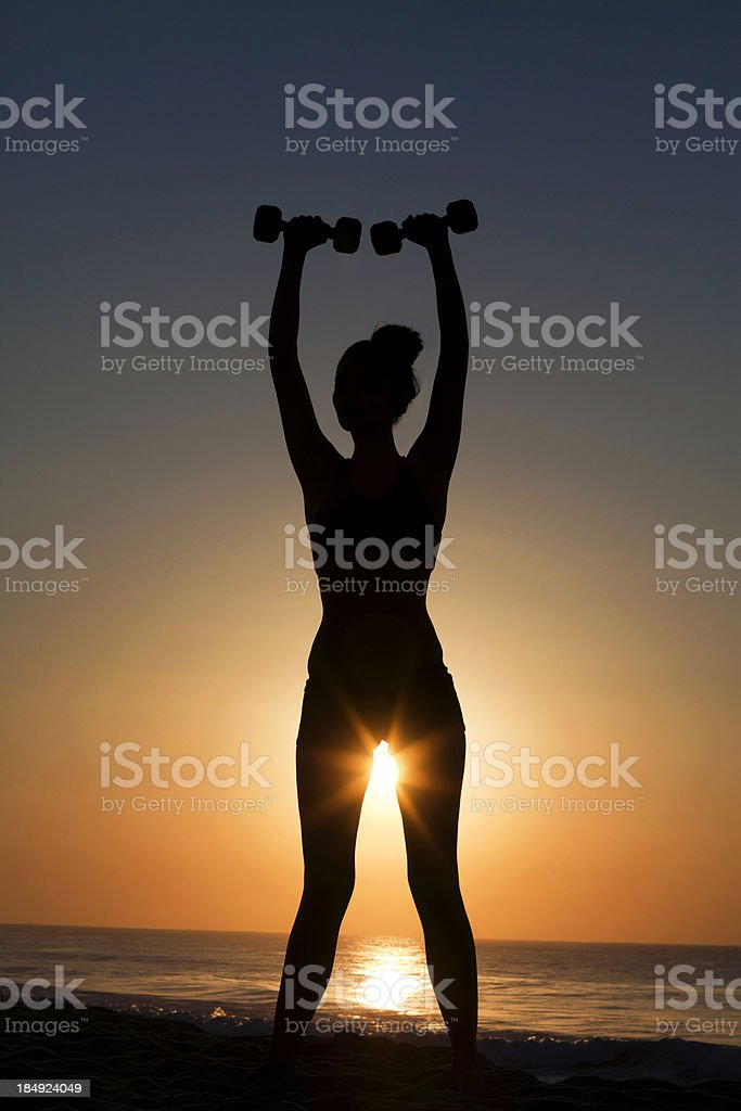 Female silhouette weight lifting  at sunrise stock photo
