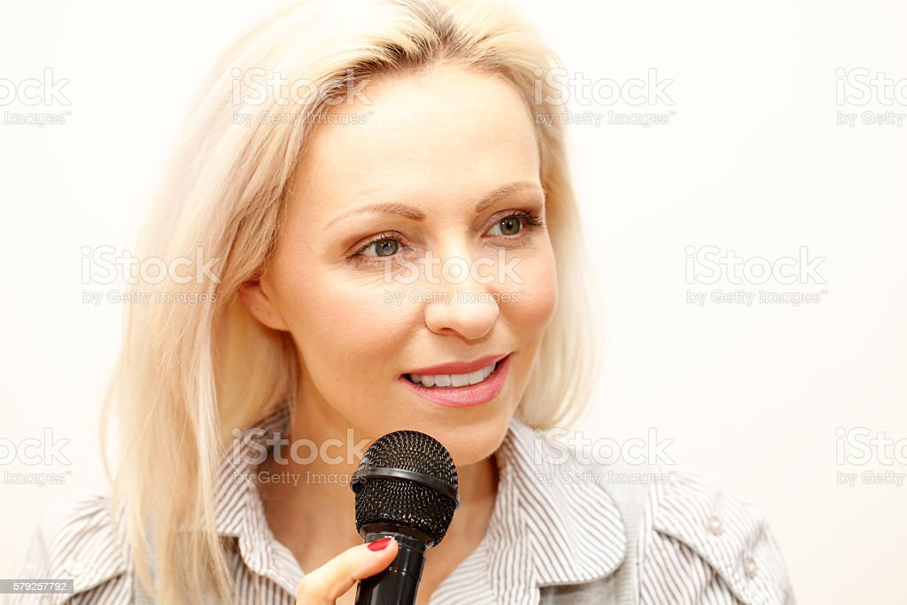 female singer holding a microphone stock photo
