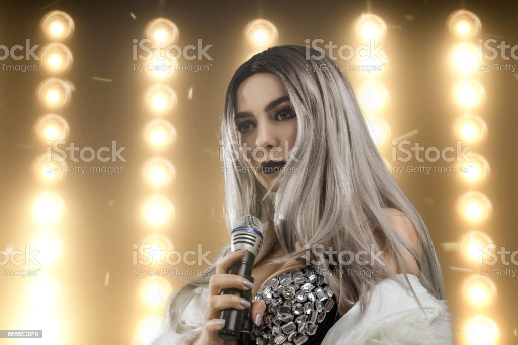 Female singer with lights on background stock photo