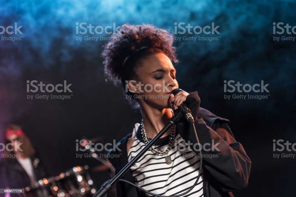 Female singer with microphone and rock and roll band performing hard rock music on stage stock photo
