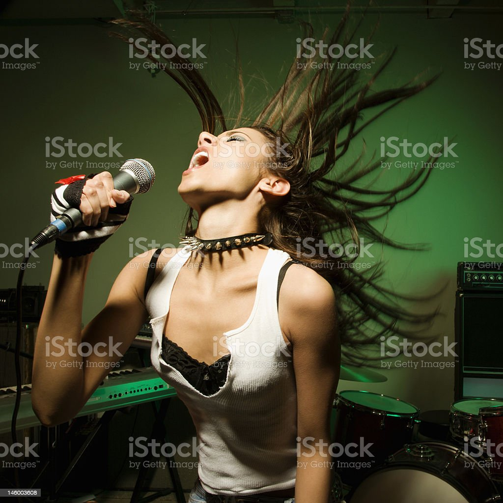 Female singing into mic. stock photo