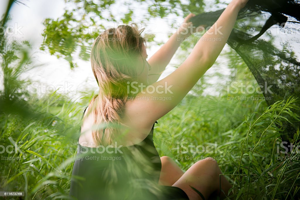 Female Sitting in Grass Field on Windy Summer Day stock photo