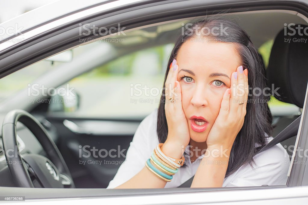 Female sitting  in the car in shock stock photo