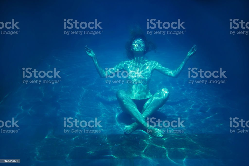 Female sitting on the bottom of pool in lotos pose stock photo