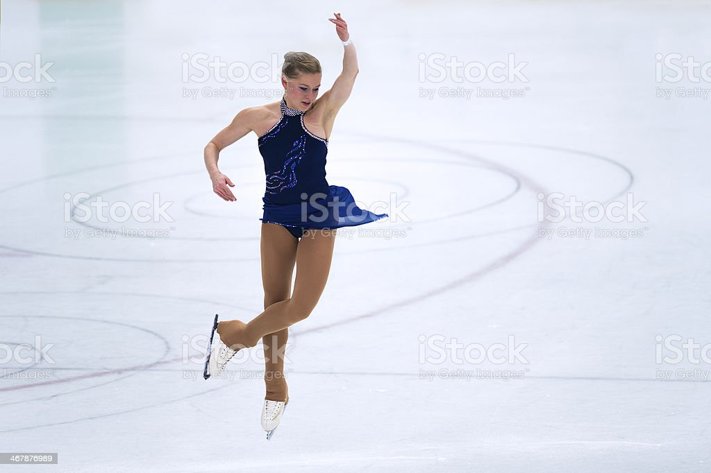 Female Skater Performing Jump During Figure Skating Competition stock photo