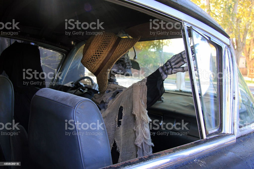 Female skeleton in hat sits in passanger side of a hearse stock photo