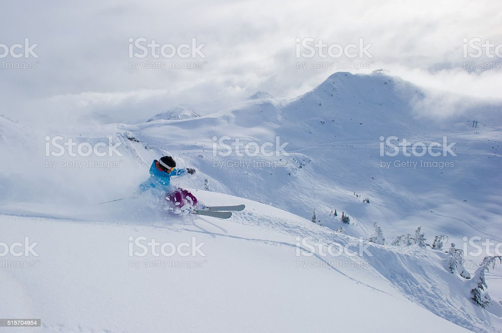 Female skier making a powder turn stock photo