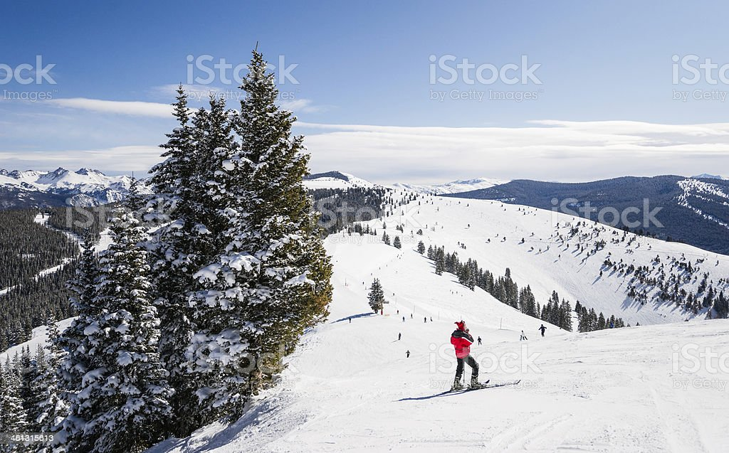 Female skier on slope looking out at Rocky Mountains stock photo