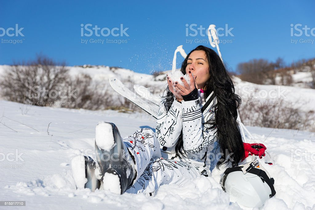 Female Skier Sitting and Enjoying Warm Sunshine stock photo