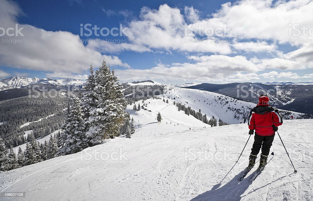 Female Skier Standing with Rocky Mountains in Background stock photo