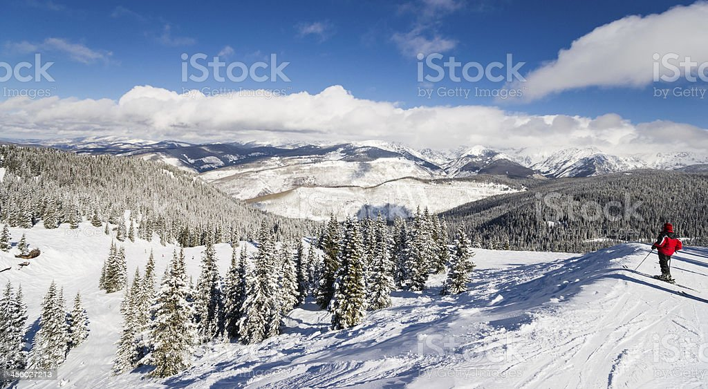 Female Skier Standing with Rocky Mountains Skiing Slopes in Background stock photo