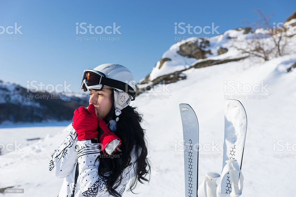 Female Skier Warming Hands on Sunny Mountainside stock photo