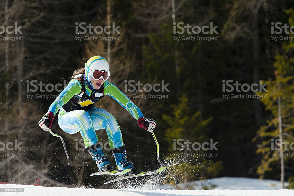 Female skiier jumping during the downhill race stock photo