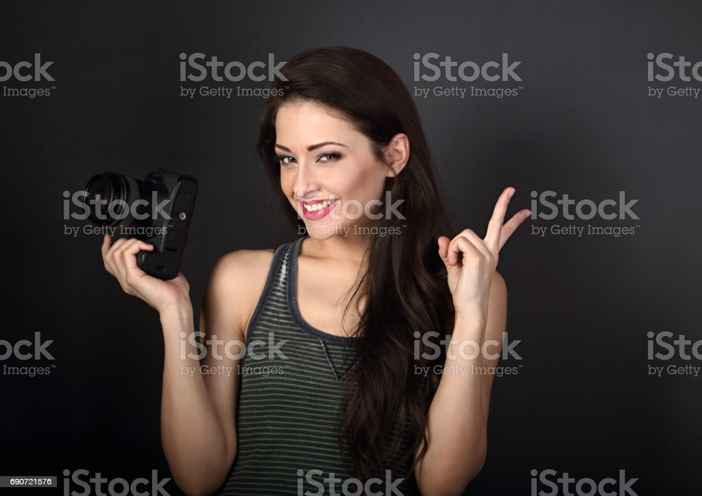 Female smiling photograph holding camera and showing v-sign victory gesture on dark grey background with empty copy space. Closeup portrait stock photo