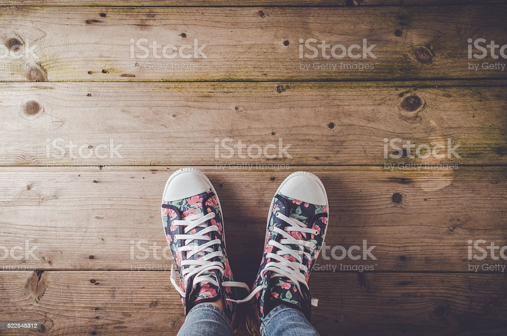 Female sneakers with floral pattern standing on wooden floor stock photo