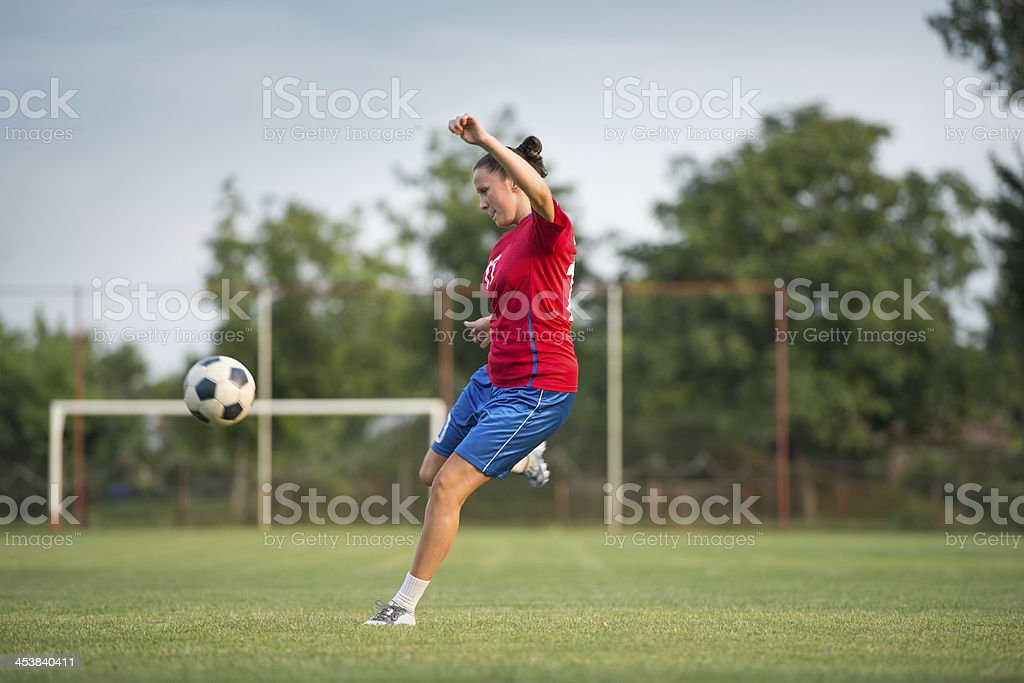 A female soccer player about to kick a ball stock photo
