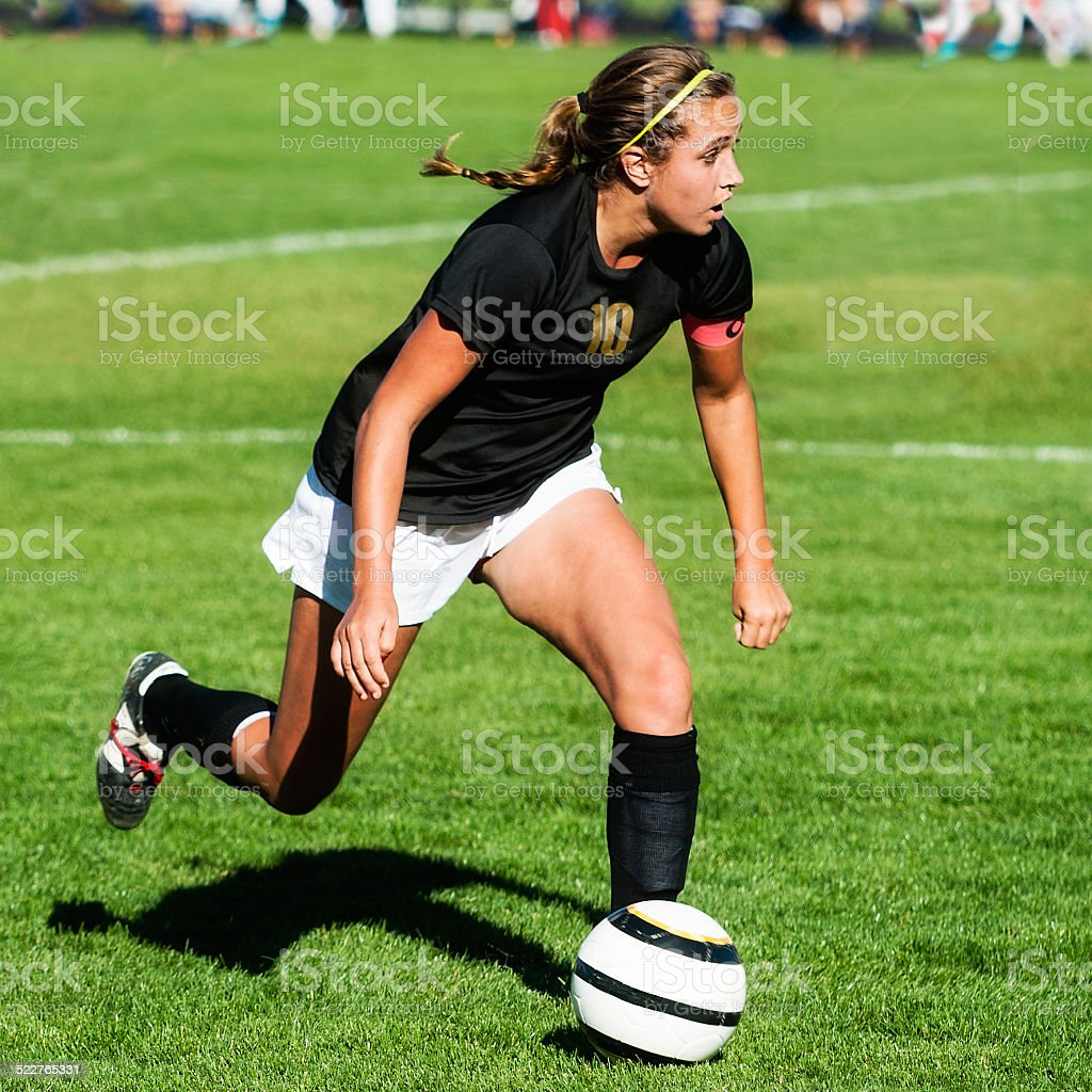 Female Soccer Player Hyper Intensity Black Jersey Eyes Up Downfield stock photo