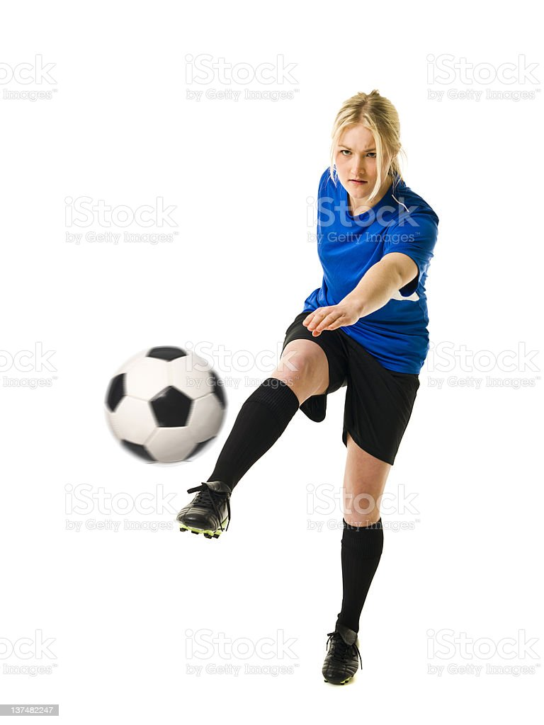 A female soccer player in a blue jersey kicking a ball royalty-free stock photo