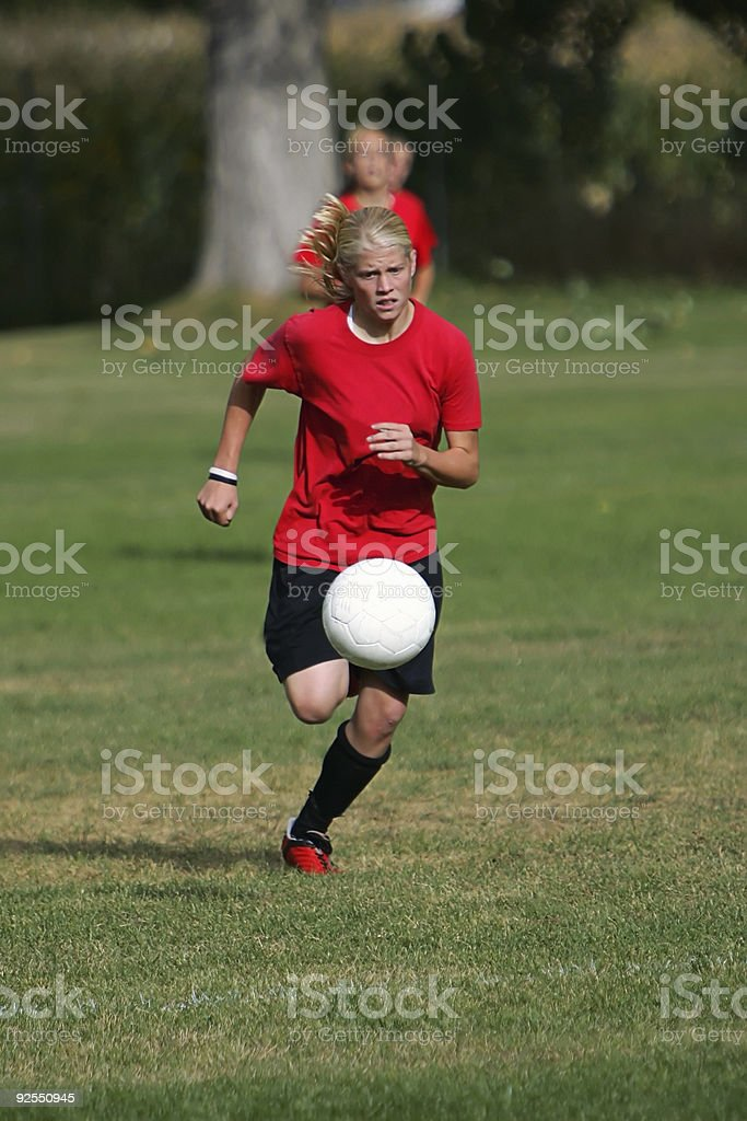 Female Soccer Player in Red Chases Bouncing Ball royalty-free stock photo