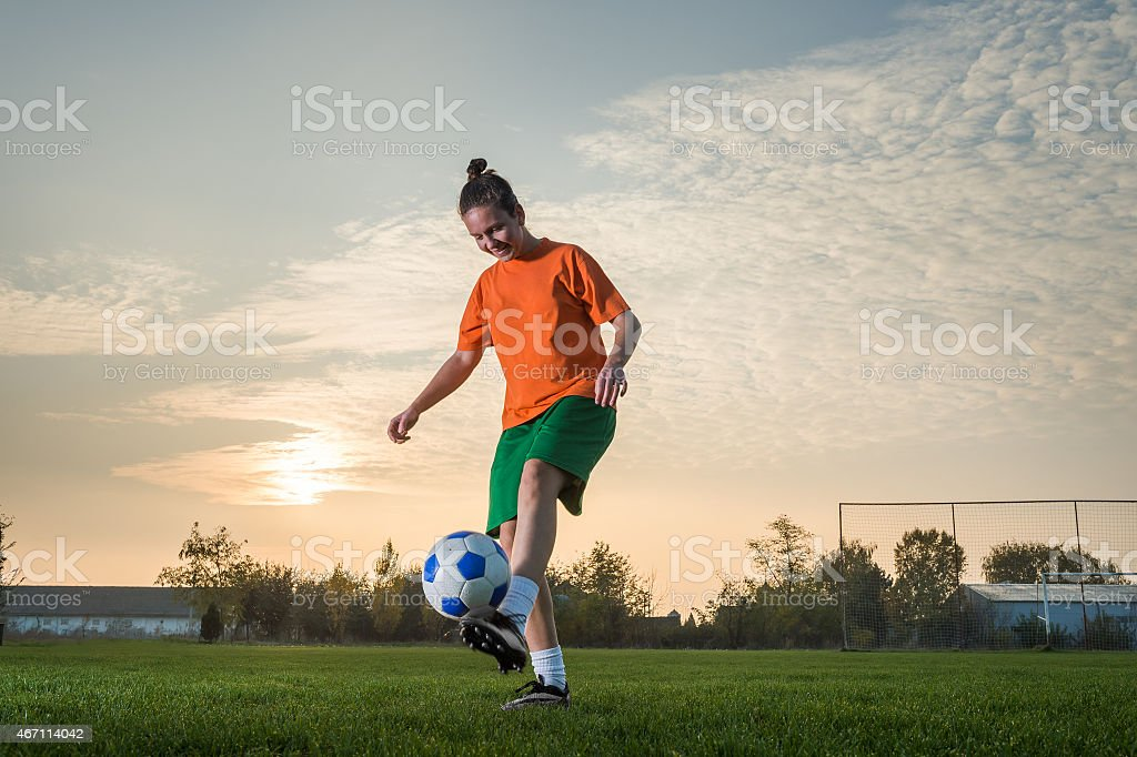 Female soccer player kicking ball around in an open field stock photo