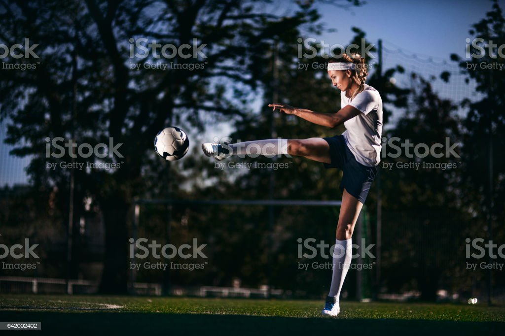 Female soccer player kicking ball stock photo