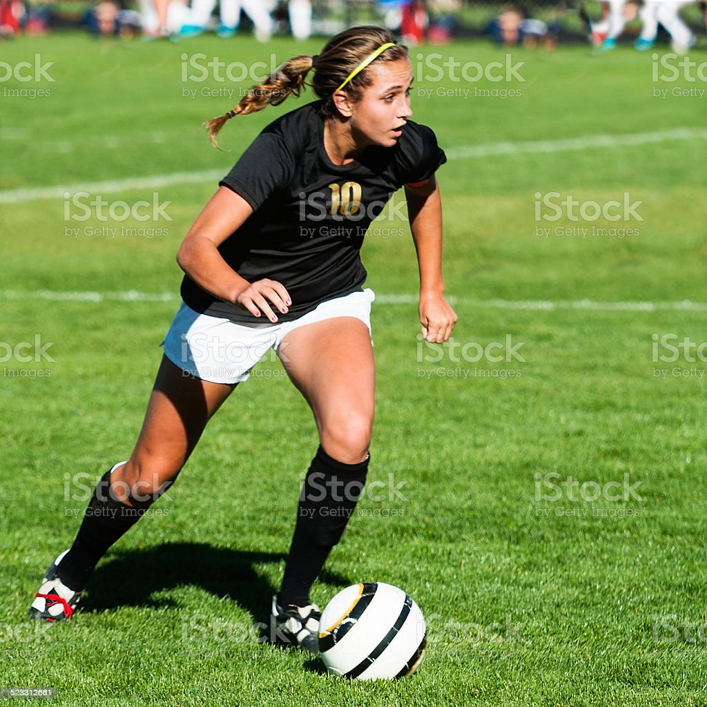 Female Soccer Player Showing Mega Intensity with Eyes Up Downfield stock photo