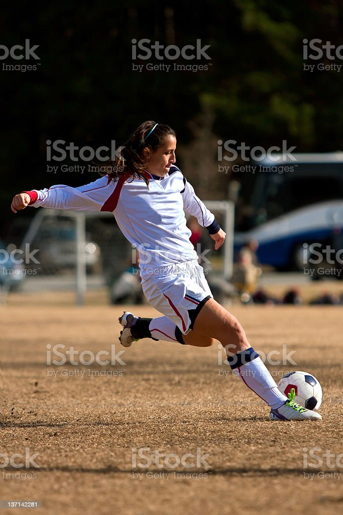 Female Soccer Player Winds Up To Kick Ball stock photo