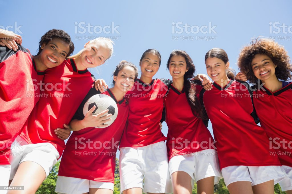 Portrait of confident female soccer team with ball against clear blue...