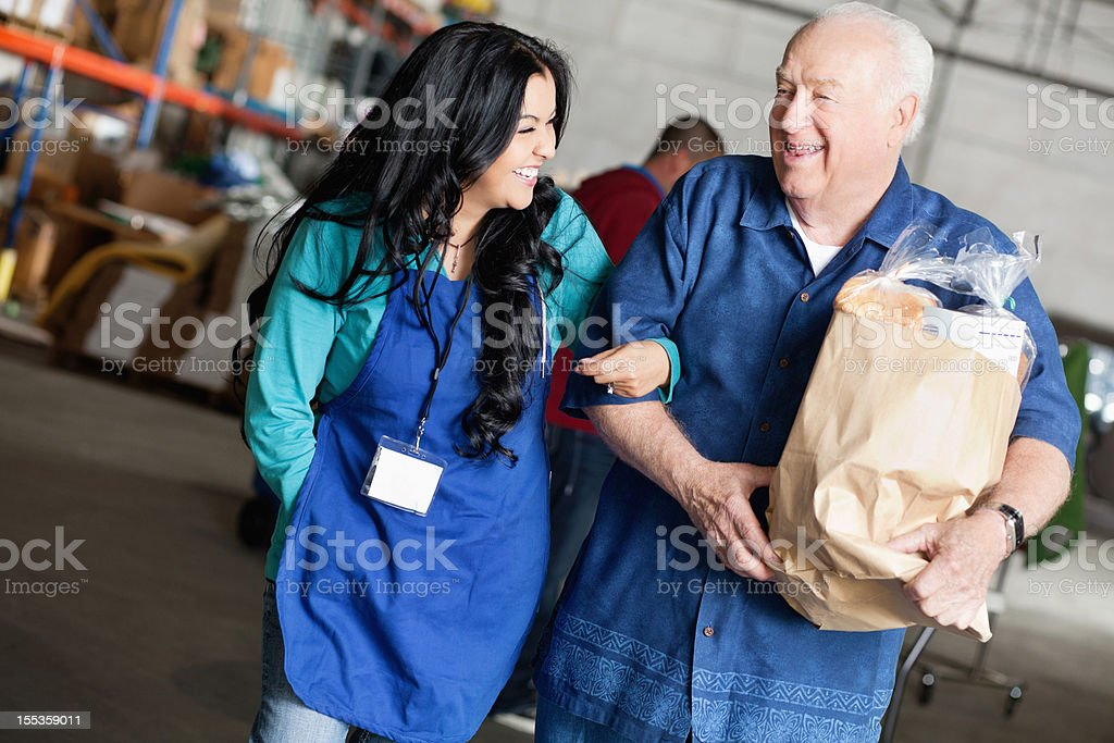 Female social worker laughing with senior man carrying groceries royalty-free stock photo