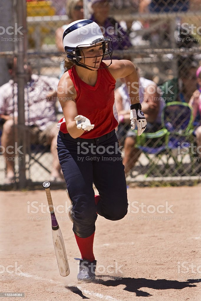 Female Softball Player Runs To First Base royalty-free stock photo
