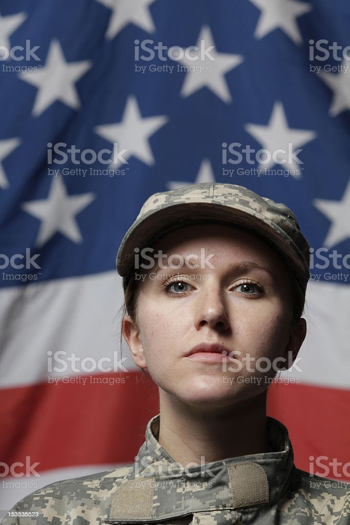 Female soldier in front of US flag, vertical stock photo