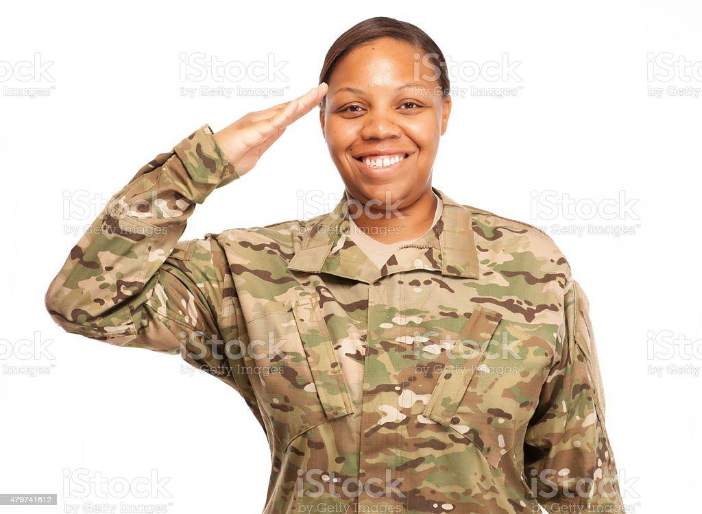 Female soldier in multicam uniform saluting. stock photo