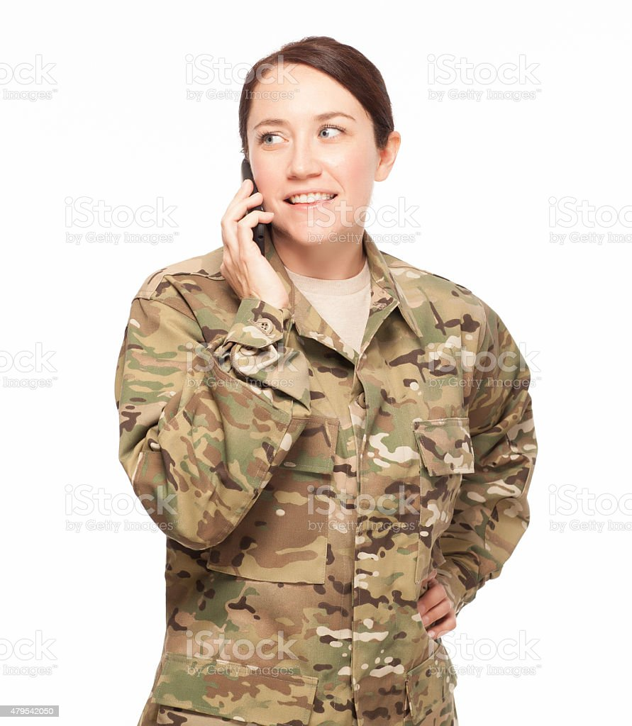 Female soldier looking away on phone. stock photo
