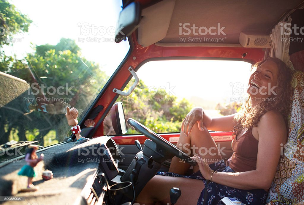 Female solo traveller or backpacker laughing driving campervan stock photo