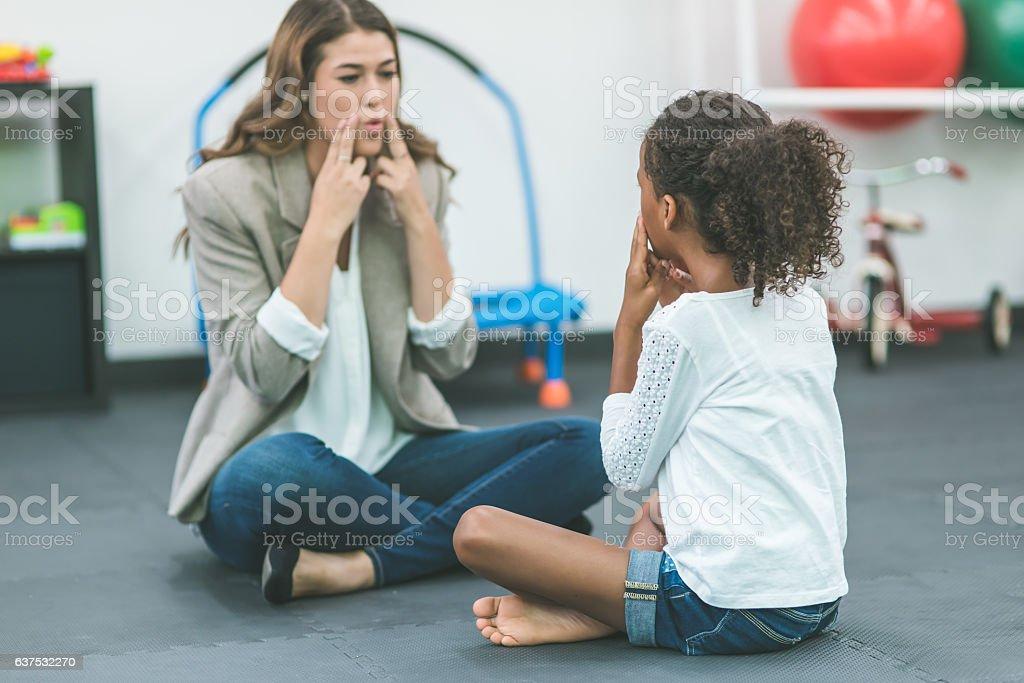 A female speech pathologist is teaching a child patient stock photo