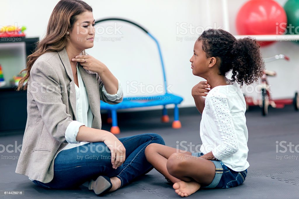 Female speech therapist assisting young African American girl stock photo