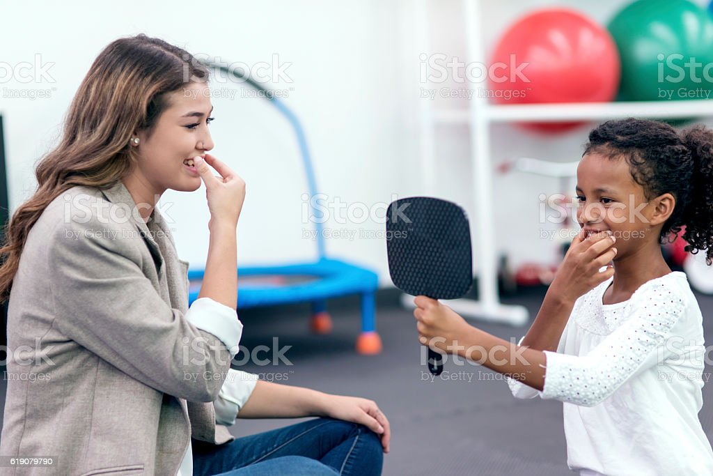 Female speech therapist helping young African American girl in rehab stock photo