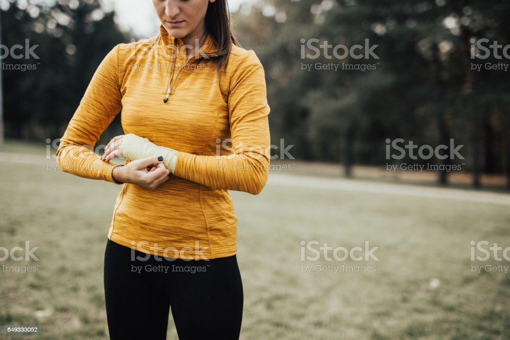 Female sports persone wrapping hands stock photo