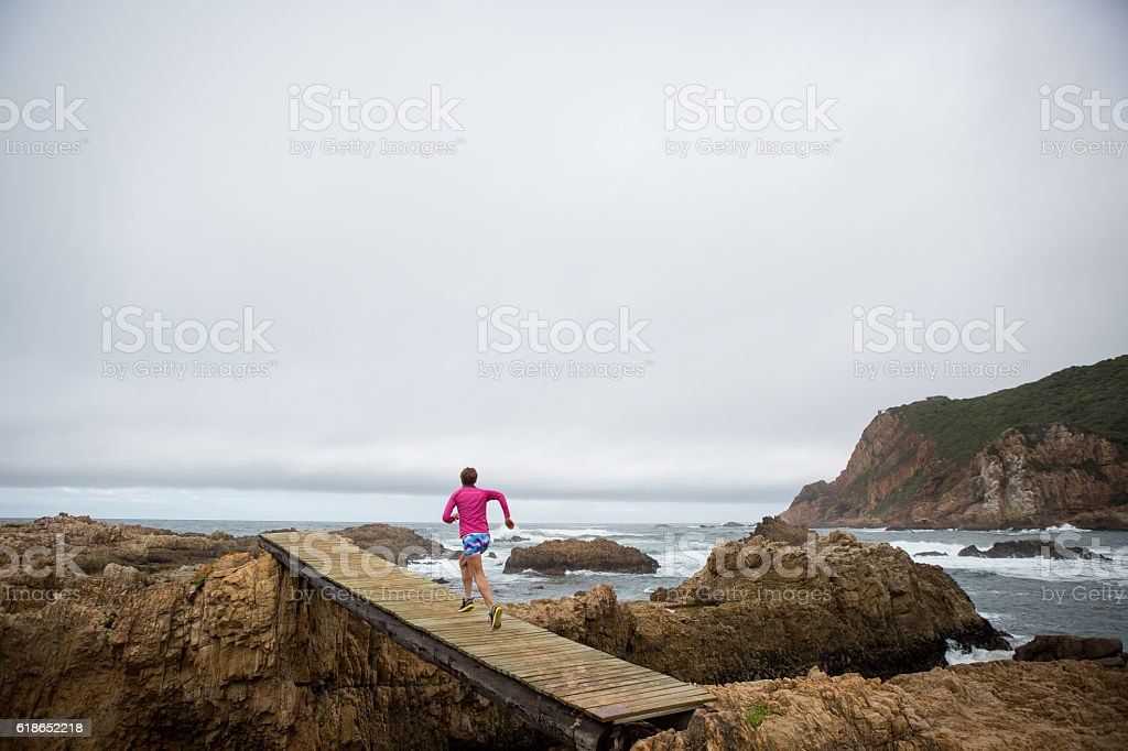 Female sportswoman enjoying view over the rocky ocean stock photo