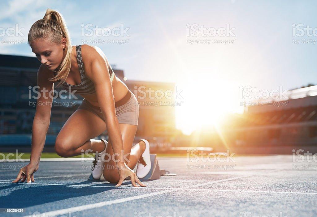 Female sprinter in track starting blocks stock photo